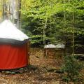 Surely Handmade Yurts - 'Secluded Forest' 10' diameter.  Showing wide view with canoe and wood pile.